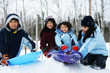 Four kids enjoying winter outdoors sledding