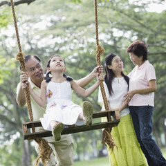 Family outdoors at park with young girl on swing