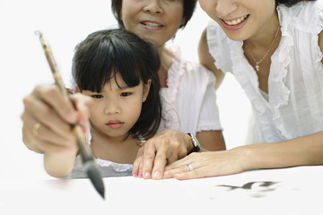 Two women and young girl indoors painting Chinese letters