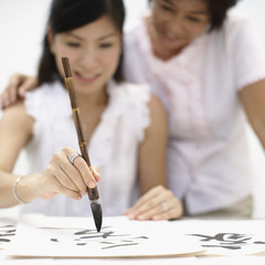 Two women indoors painting Chinese letters
