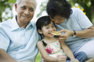 Couple and young girl outdoors having a snack