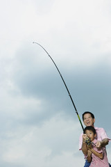 Man helping young boy outdoors fishing