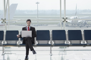 Businessman in airport with laptop and mobile phone