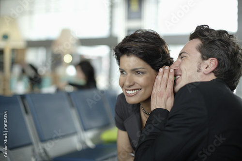 Man in airport whispering in woman's ear