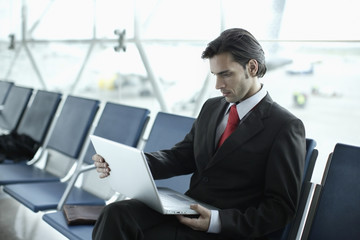 Businessman in airport with laptop