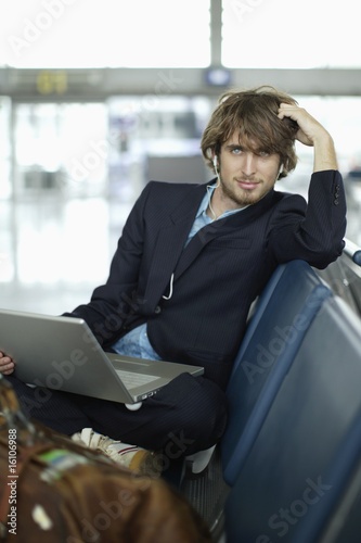 Man wearing earphones in airport with laptop
