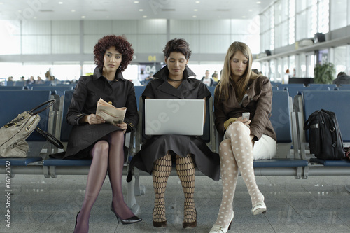 Three businesswomen in airport with laptop and newspaper