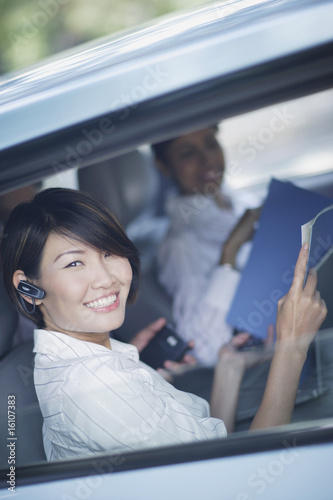 Three businesspeople in car with paperwork