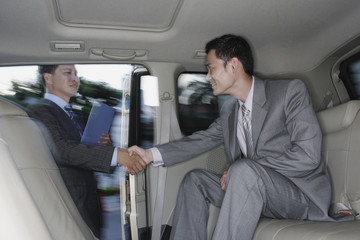 Businessmen in limousine shaking hands with businessman standing outside