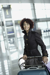 Woman in airport with luggage cart