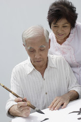 Couple indoors painting Chinese letters