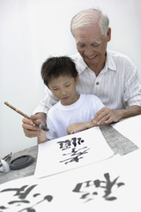 Man and young boy indoors painting Chinese letters