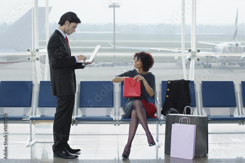 Businessman in airport on laptop near woman with shopping bags