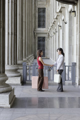 Two businesswomen outdoors by building shaking hands