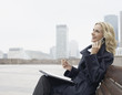 businesswoman outdoors on her mobile phone with paperwork laughing