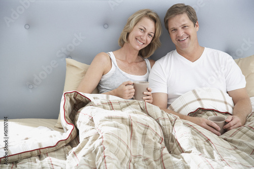 Couple sitting in bed with mugs