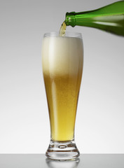 Glass of beer being poured indoors