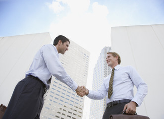 Two businessmen outdoors shaking hands