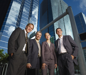 Four businesspeople outdoors by buildings
