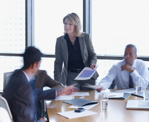 Businesswoman handing papers to three businesspeople in a boardroom