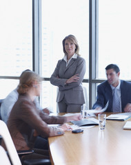Four businesspeople in a boardroom with one in focus