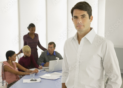 Four businesspeople in a boardroom with a laptop with a businessman in foreground