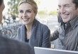 Couple and man on outdoor patio with laptop