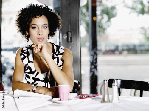 Woman sitting in restaurant with paperwork