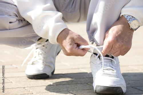 靴紐を結ぶ男性の手元