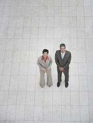 Two businesspeople standing indoors looking at camera