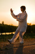woman in white suit make's taiji chuan exercise - 10