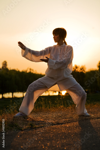 woman in white suit make's taiji chuan exercise - 9