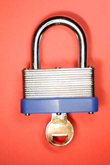 Padlock and key on red