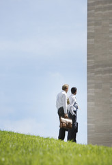 Two businessmen outdoors by a wall
