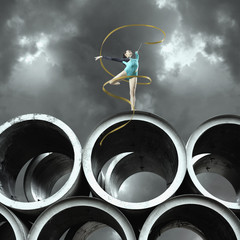 Woman gymnast outdoors on large cement cylinders posing with ribbon