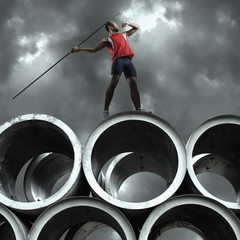 Javelin thrower standing outdoors on large cement cylinders