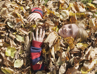 Young girl lying buried in leaves outdoors