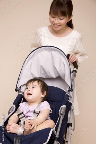 ベビーカーに赤ちゃんを座らせ散歩する母親