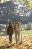 Couple outdoors walking a dog by a lake