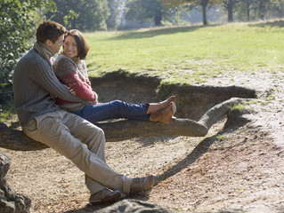 Couple outdoors sitting on large tree branch