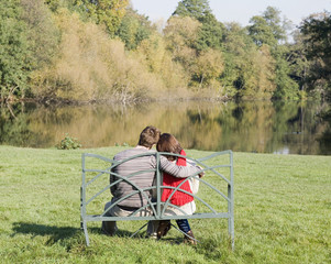 Couple outdoors sitting on a bench by a lake