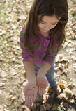 Young girl outdoors holding an earthworm