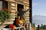 Mature couple sitting in front of alpine hut, talking to farmer