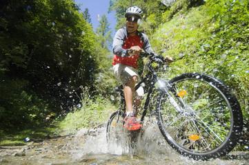 Mountainbiker überquert Bach
