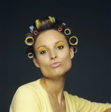 Woman with rollers in hair pouting, close-up, portrait