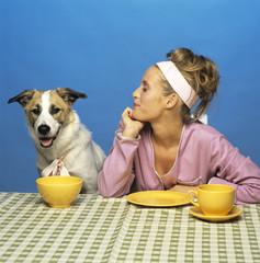 Junge Frau und Hund sitzen am Tisch vor ihrem Geschirr