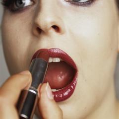 Junge Frau beim Auftragen von Lippenstift