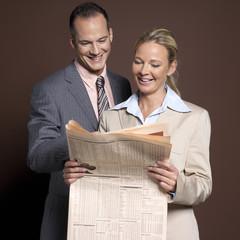 Geschäftsmann und Geschäftsfrau, Mann mit Zeitung