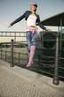 Junge Frau springt vom Geländer