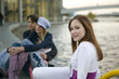Junge Frau sitzt am Fluss, Paar im Hintergrund